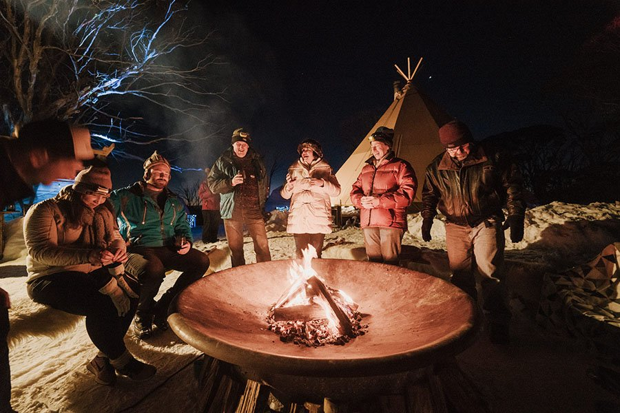 Group drinks around the fire at the eco-village